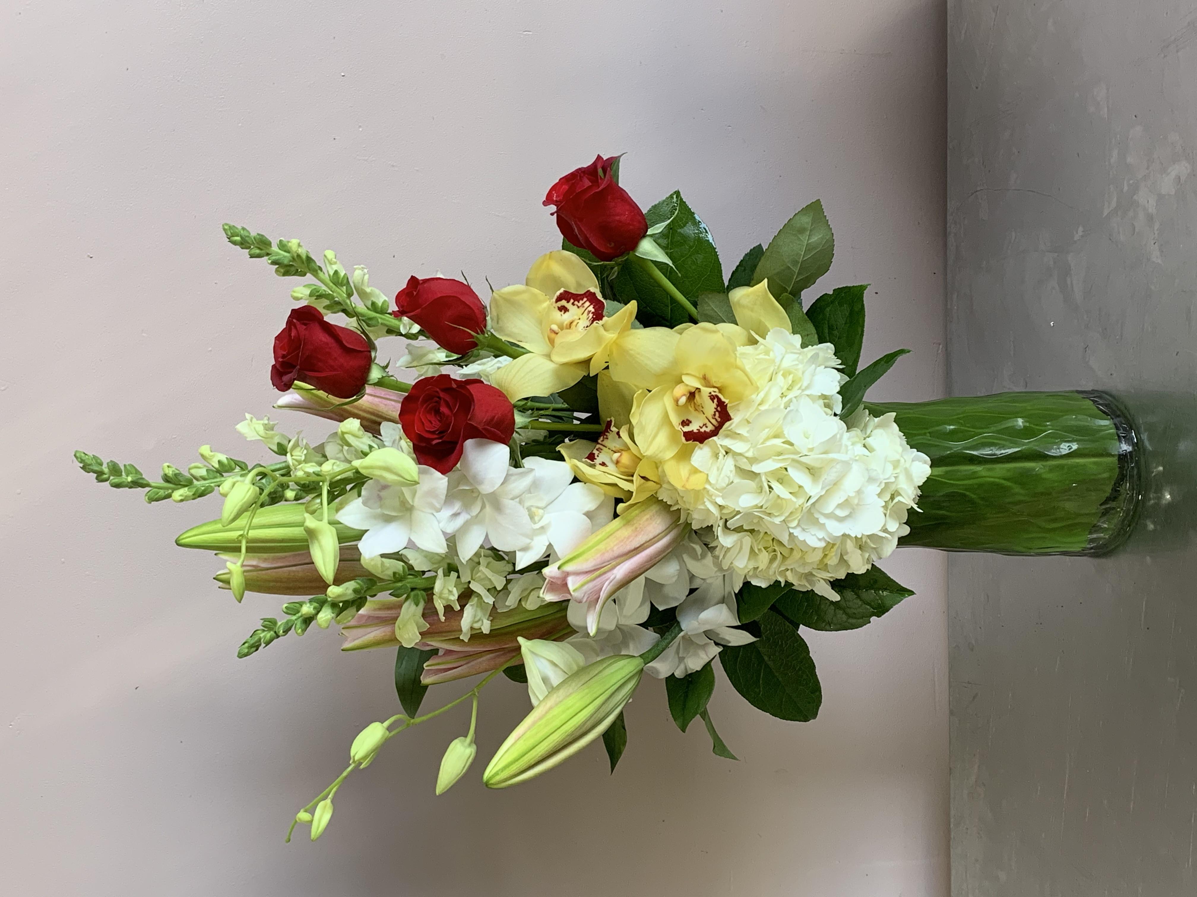 A tall vase of Roses Velene's Floral